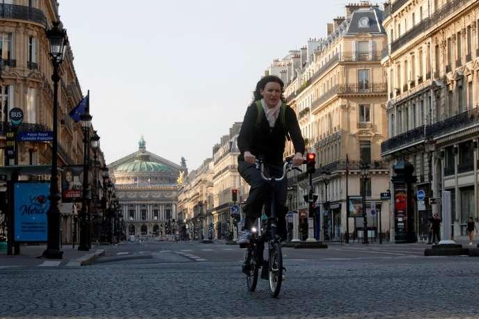 Une Parisienne arpente en vélo le quartier de l'Opéra, à Paris, le 10 avril.