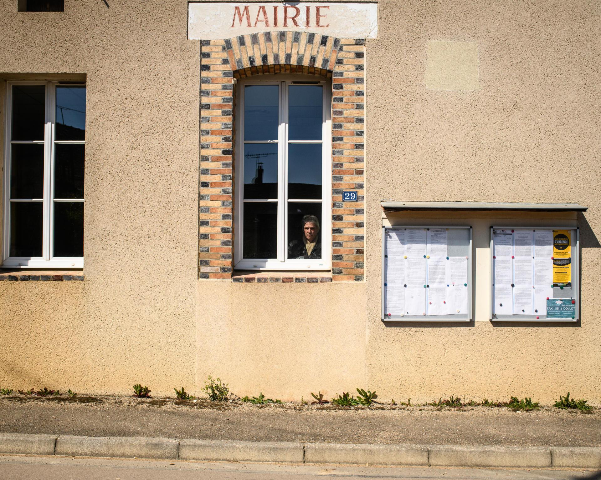 Jean-Jacques Noël, maire du village de Dollot, pose derrière une fenêtre de la salle des fêtes pendant la période de confinement dû au coronavirus.