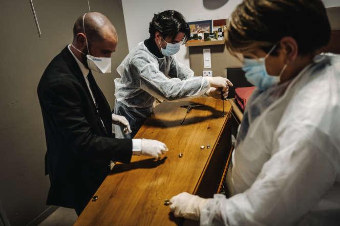 Des employés des pompes funèbres ferment le cercueil d'une dame décédée dans la nuit du Covid-19 dans un Ehpad, à Paris, le 18 mars.