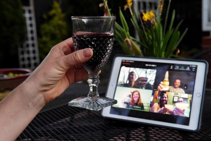 Une femme prend l'apéritif avec des amis, lors d'un happy hour virtuel, au milieu de la crise due au nouveau coronavirus, à Arlington, aux Etats-Unis.
