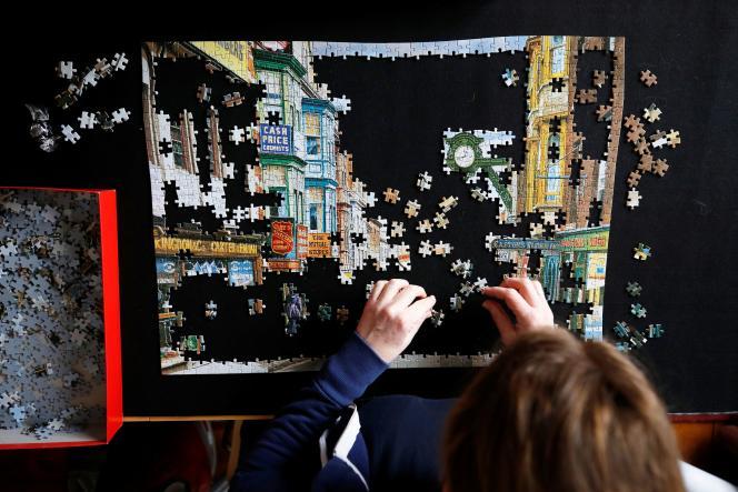 Une femme fait un puzzle à Manchester, en Angleterre, le 12 avril.