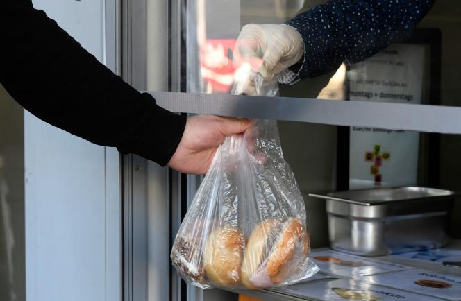 Un sans-abri emporte un sac de nourriture, dans un centre social, le 17 mars à Dortmund (Allemagne).