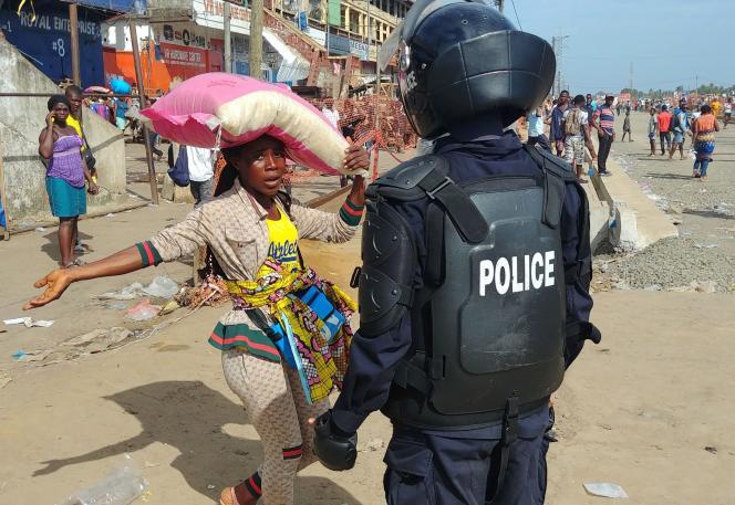 Un agent de police fait respecter les mesures de confinement sur un marché de Monrovia, au Liberia, le 11avril 2020.