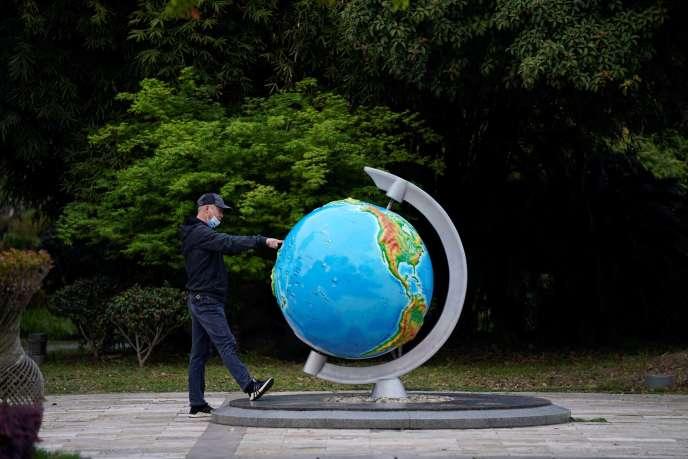 Un homme fait tourner un globe terrestre dans un parc, le 4 avril à Wuhan (Chine).