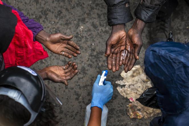 Des sans-abri qui attendent de recevoir des paniers de nourriture de donateurs privés se font désinfecter les mains le 13 avril 2020 dans le centre-ville de Johannesburg.
