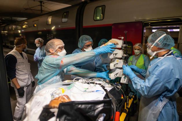 Des soignants s'apprêtent à faire embarquer un malade à bord de l'un des deux TGV.