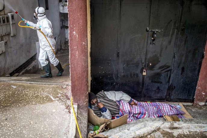 Un sans-abri à Rabat, tandis qu'un agent du ministère marocain de la santé désinfecte la rue pour lutter contre le coronavirus, le 22mars 2020.