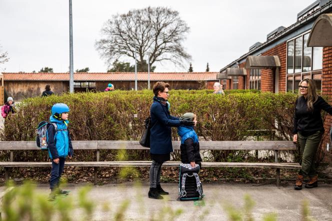 Des parents et leurs enfants font la queue pour entrer dans leur école, le 15 avril àGladsaxe (Danemark).