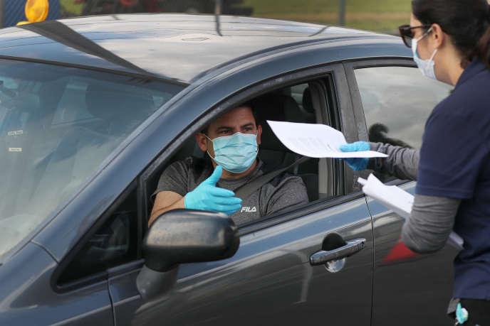Un automobiliste vient retirer une demande d'inscription au chômage, dans la ville de Floride d'Hialeah, le 8 avril.