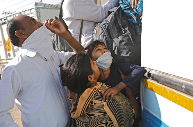 Les familles peinent à monter à bord des bus bondés deGhaziabad (banlieue de New Delhi), le 29 mars.