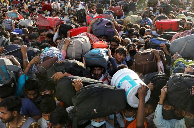 En Inde, le 28 mars, des travailleurs pauvres tentent de retourner dans leurs villages. Ici, devant une gare routière de New Delhi.