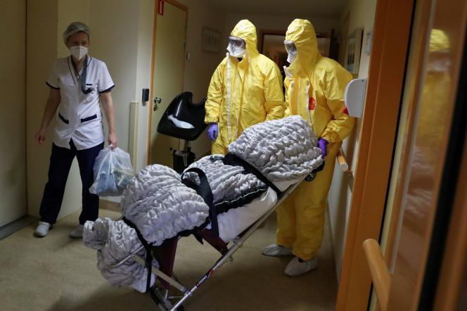 Dans une maison de retraite, les employés de la morgue transportent le corps d'une personne morte du Covid-19, à Bruxelles, le 14 avril.