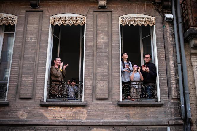 Mardi 14 avril, Toulouse, 20 heures, des familles de la rue Raymond-IV applaudissent à leur fenêtre pour rendre hommage aux personnels hospitaliers.