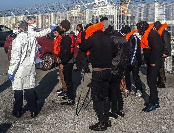 Un pompier prend la température de migrants récupérés au large de Calais alors qu'ils tentaient la traverée vers la Grande-Bretagne, le 17 avril.