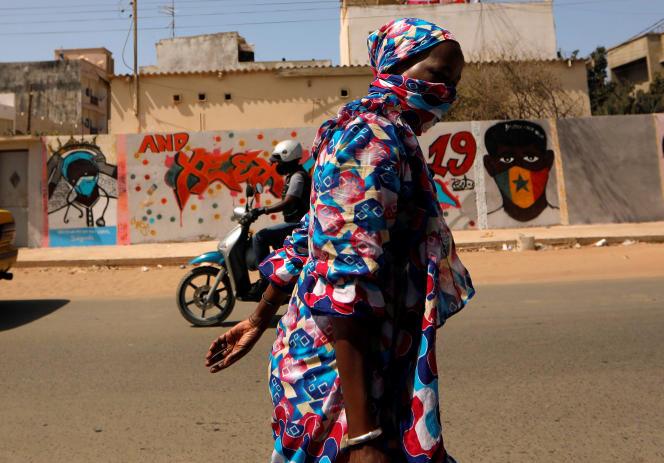 Une Sénégalaise passe devant un graffiti incitant à«rester chez soi», à Dakar, le 16avril 2020.