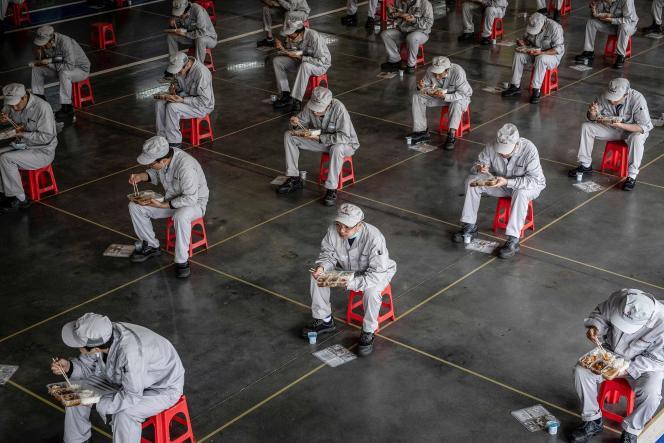 Pause déjeuner pour les employés de l'usine automobile Dongfeng Honda à Wuhan, dans la province chinoise du Hubei, le 23 mars.
