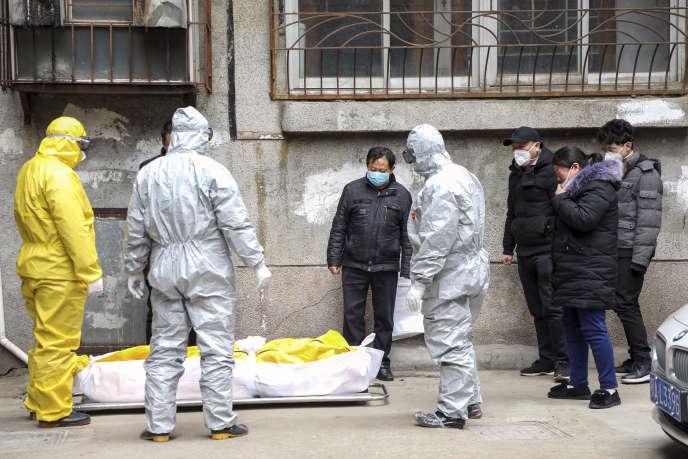 Des employés funéraires transportent le corps d'une personne suspectée d'être morte du Covid-19, le 1erfévrier à Wuhan, en Chine.