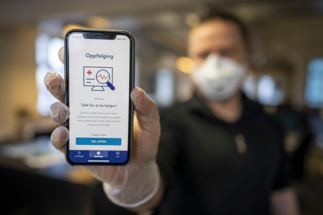 Le 17 avril, à Oslo, un homme montre son smartphone muni d'une application de traçage l'alertant s'il s'est trouvé près d'une personne infectée par le Covid-19.