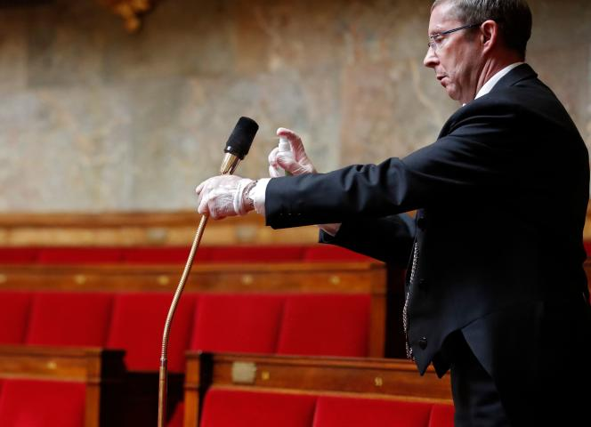 Désinfection d'un micro à l'Assemblée nationale à Paris, le 17 avril.