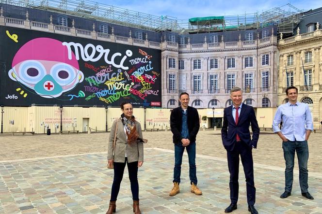 Yann Bubien (2e en partant de la droite) et trois membres du personnel soignant du CHU de Bordeaux posent devant la fresque de l'artiste bordelais Jofo, inaugurée le 17 avril, place de la Bourse, à Bordeaux.