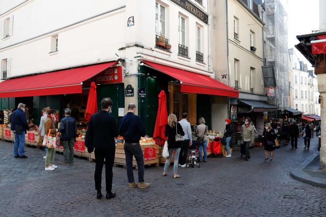 Rue Mouffetard, à Paris, le 19 avril, les client de ce primeur gardent les distances recommandées, pendant le premier confinement.