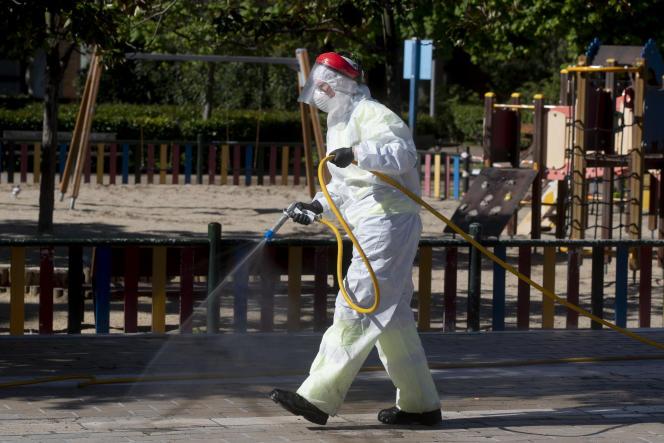 Un employé municipal désinfecte les abords d'un jardin d'enfants à Madrid, le 20avril. Les enfants de moins de 12ans pourraient être autorisés à sortir à nouveau ponctuellement en Espagne à partir de la semaine prochaine.