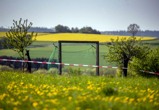 A tape barrier is fixed near a makeshift soccer goal on a meadow in Obernhain near Frankfurt, Germany, Monday, April 20, 2020. Due to the coronavirus all soccer games are cancelled. (AP Photo/Michael Probst)