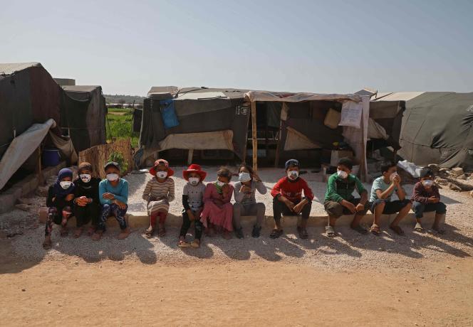 Des enfants syriens avec des masques décorés par des artistes dans un camp de déplacés à Dana, dans la province d'Idlib (nord-ouest de la Syrie), le 20 avril.