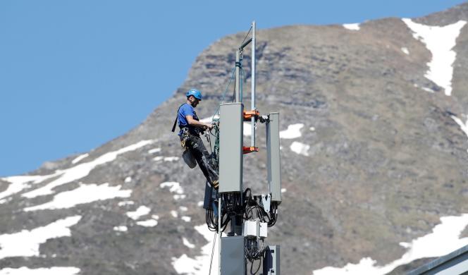 Un technicien installe les antennes 5G de l'opérateur télécom Swisscom sur un mât, dans la station de Lenzerheide, en Suisse, le 13 juin 2019.