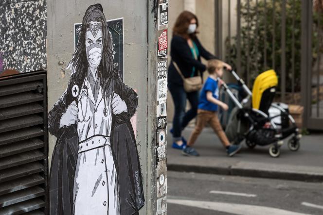 Une femme et ses enfants passent près d'une fresque représentant « Super infirmière» de l'artiste Combo, à Paris, le 21 avril.