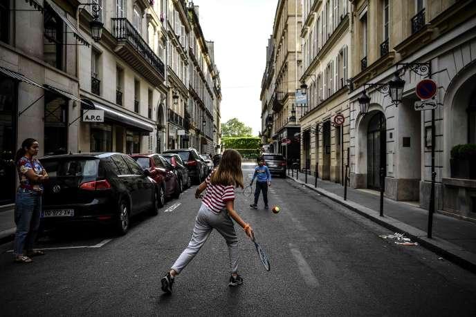 Des enfants jouent au tennis dans les rues désertées de Paris, le 21 avril.