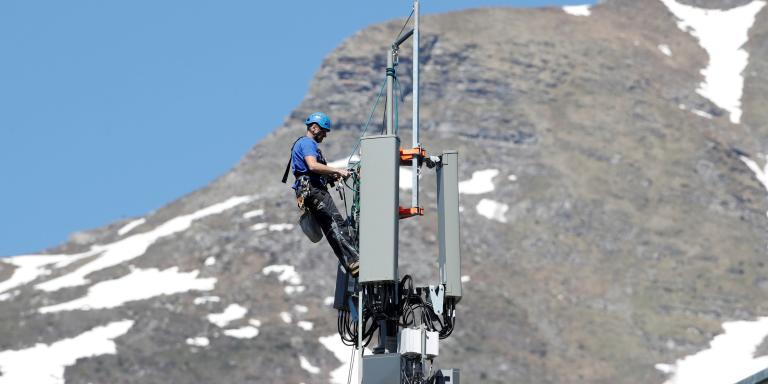 FILE PHOTO: A technician is roped up as he installs 5G antennas of Swiss telecom operator Swisscom on a mast in the mountain resort of Lenzerheide, Switzerland June 13, 2019. REUTERS/Arnd Wiegmann/File Photo