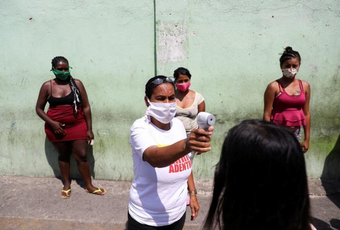 La température d'une femme est prise à un poste de contrôle dans le bidonville de Catia, à Caracas, lors de l'épidémie due au coronavirus, le 15 avril 2020.