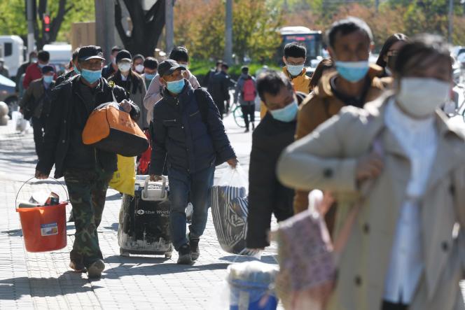 Des passants devant une station de métro de Pékin, en Chine, le 23 avril 2020.