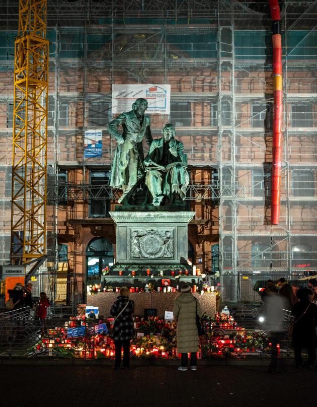 Hanau (Hesse), le 22 février. Fleurs, bougies et photos entourent la statue des frères Grimm, originaires de la ville. Des passants ont ainsi rendu hommage aux victimes du massacre perpétué le 19 février par un extrémiste de droite allemand de 43 ans.