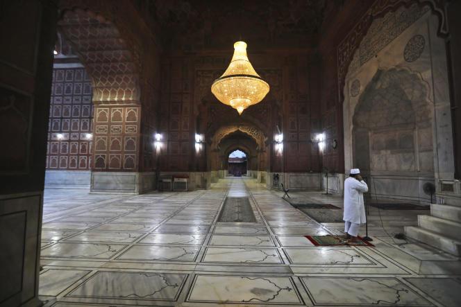 Un prêtre musulman appelle à la prière du soir depuis la mosquée de Jama Masjid, habituellement bondée au cours du mois sacré du ramadan, à New Delhi (Inde), le samedi 25 avril 2020.