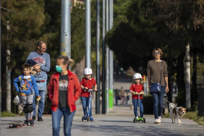 Des familles se promènent sur un boulevard de Barcelone (Espagne), dimanche 26 avril 2020, alors que les enfants de moins de 14 ans sont autorisés à sortir pour la première fois depuis six semaines.