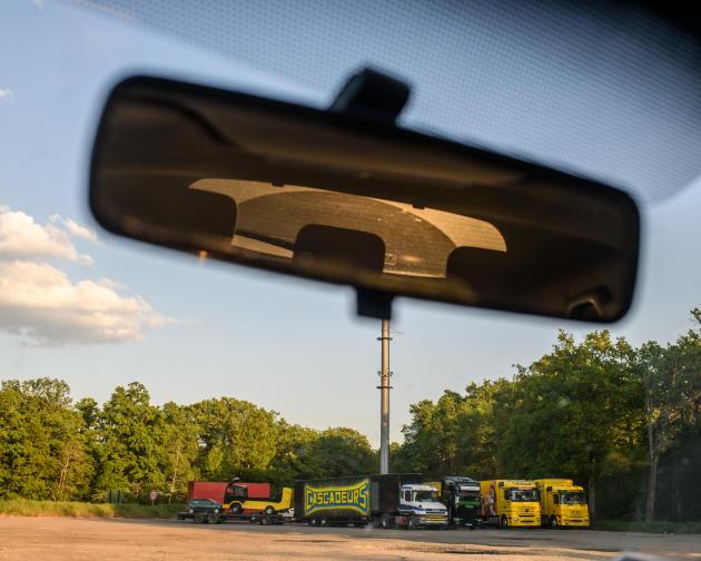 Des camions de forains garés sur le parking d'un restaurant fermé, le long de la départementale D2007.