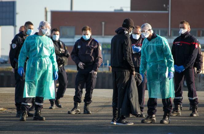 Des officiers de police et des professionnels de la santé interpellent un migrant à Calais (Pas-de-Calais), le 7 avril.