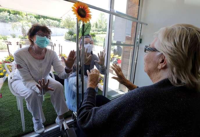 Cette résidente, agée de 89 ans, reçoir la visite de ses filles derrière une vitre à l'Ehpad Les Figuiers, à Villeneuve-Loubet (Alpes-Maritimes), le 23 avril.