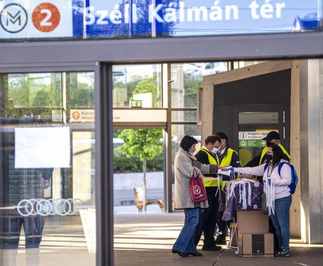 Une employée des transports publics distribue des masques à la station de métro Szell-Kalman, à Budapest (Hongrie), le 27 avril.