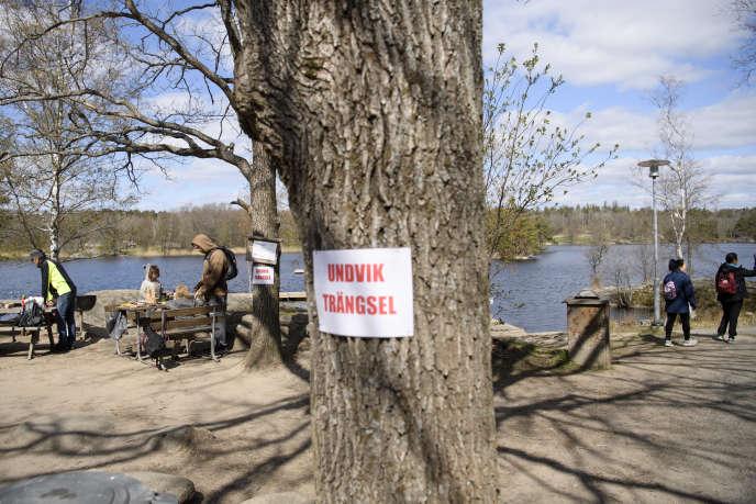 «Evitez l'affluence», intime un panneau dans la zone de loisirs Hellasgarden, dans la banlieue de Stockholm, en Suède, le 26 avril.