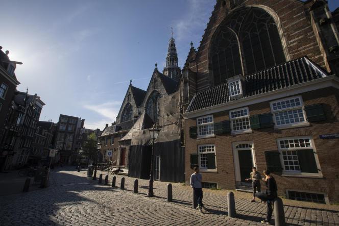 Trois personnes conversent en respectant ladistanciation devant la Oude Kerk d'Amsterdam, le 24 avril.