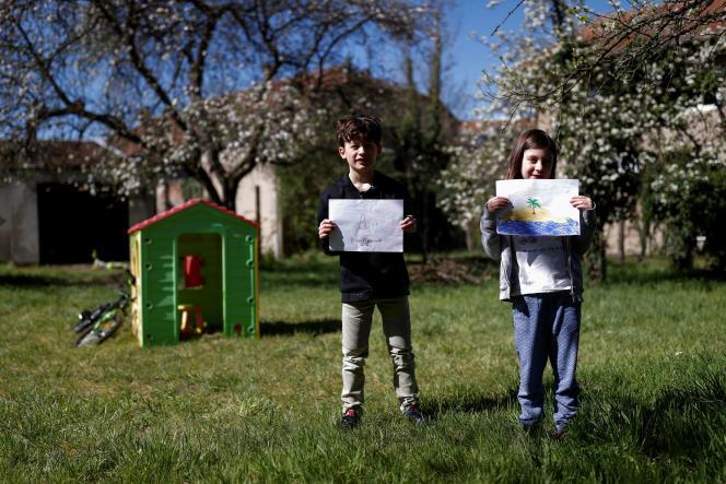 Arthur, 9 ans, et Zoe Klein, 6 ans, dans le jardin, où il est facile de s'adonner au land art et dejouer avec les éléments. Dans l'est de la France, le 14 avril.
