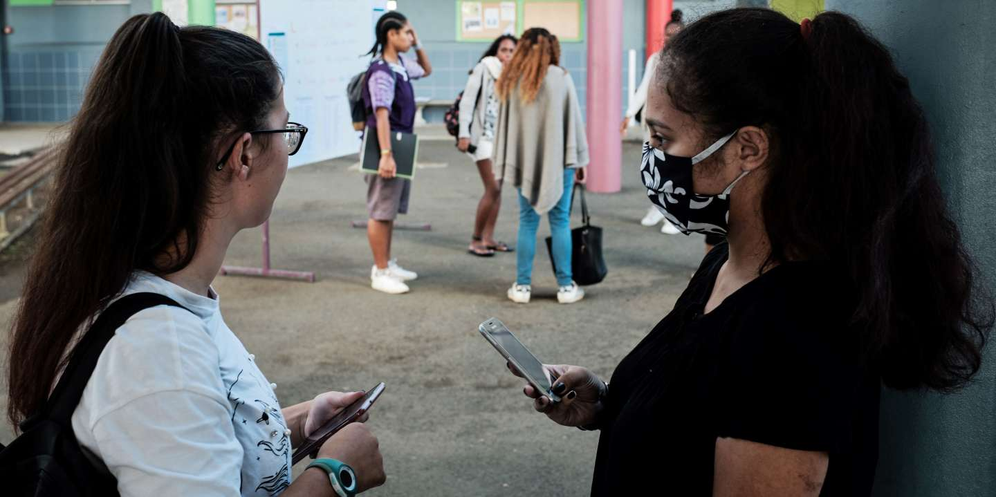 A highschool student wearing a facemask for protective measures, speaks with a friend upon their arrival at the Lycee Laperousse school, in Noumea, on the French Pacific island of New Caledonia, on April 22, 2020 on the opening day of the schools following a for weeks lockdown installed by the government to curb the spread of the COVID-19, (the novel coronavirus).  / AFP / Theo Rouby