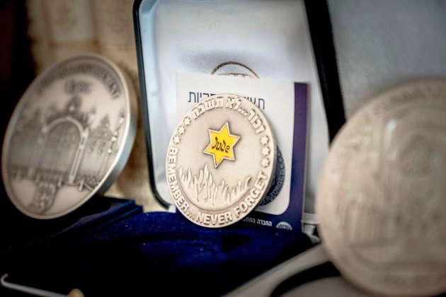 Des médailles commémoratives de la Shoah dans la bibliothèque de Benjamin Orenstein.