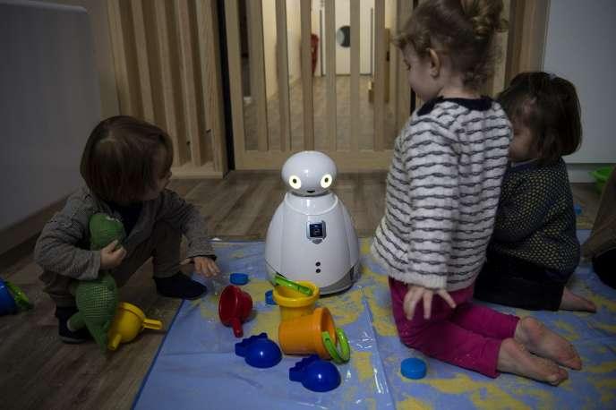 Des enfants jouent avec un robot dans une crèche, à Paris, le 1er mars 2018.