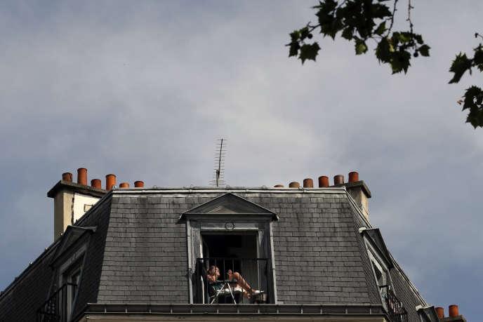 Une femme sur son balcon, à Paris, le 21 avril.
