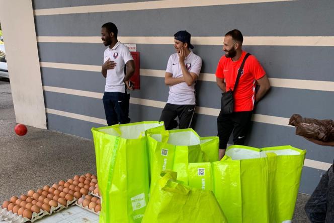 Des joueurs seniors du Vénissieux Football Club participent à une opération de distribution de nourriture à destination de personnes démunies, à Vénissieux (Rhône), le 24 avril.