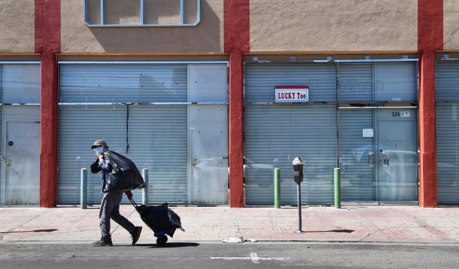 Un homme passe devant les devantures fermées du quartier de la mode, dans le centre de Los Angeles, le 22 avril.